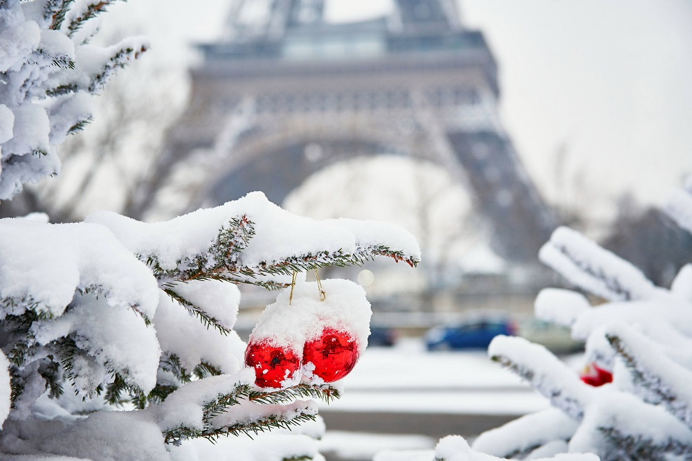 44064054 - christmas tree decorated with red balls and covered with snow on a rare snowy day in paris. eiffel tower is in the background